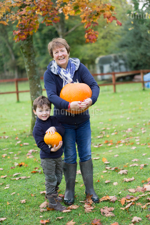 A mature woman and a small boy holding pumpkins, large and small.の写真素材 [FYI02252601]