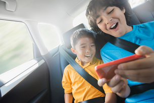 Two children travelling in the back seat of a car sharing a handheld games tablet.の写真素材 [FYI02252605]