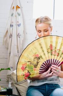 A woman holding an open Oriental fan hiding her face.の写真素材 [FYI02252609]