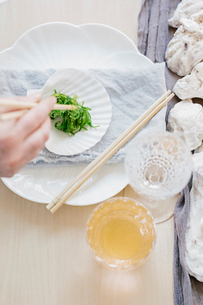 Overhead view of a table and a woman using chopsticks to eat vegetables.の写真素材 [FYI02252615]