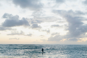 Man stand up paddling in calm waters at duskの写真素材 [FYI02252617]