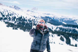 A woman on the ski slopes holding out her smart phone to take a photograph.の写真素材 [FYI02252624]