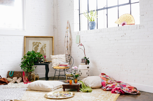 A light airy room with whitewashed walls. Cushions and possessions scattered across the floor.の写真素材 [FYI02252628]