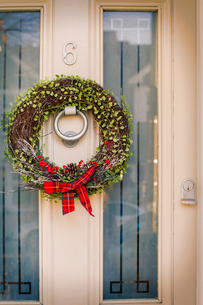 Christmas decorations. A Christmas wreath with a red bow on the front door of a house.の写真素材 [FYI02252642]