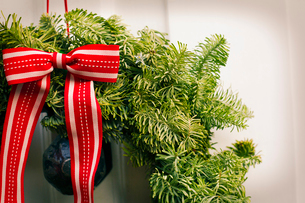 Christmas decorations. A Christmas wreath with a red bow on the front door of a house.の写真素材 [FYI02252653]