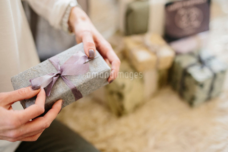 A woman holding a gift wrapped present.の写真素材 [FYI02252681]