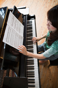 Young woman playing on a grand piano in a rehearsal studio.の写真素材 [FYI02252682]