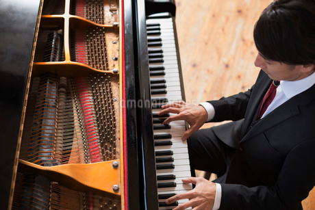 Young man playing on a grand piano in a rehearsal studio.の写真素材 [FYI02252694]