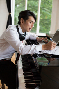 Young man sitting at a grand piano in a rehearsal studio, annotating sheet music.の写真素材 [FYI02252702]