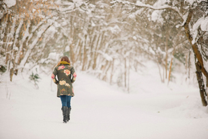 A woman walking in the snow in woodland.の写真素材 [FYI02252703]