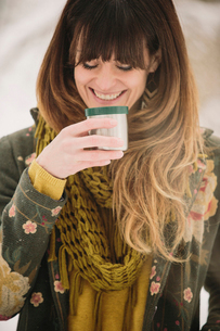 A woman in snow in winter, having a warm drink.の写真素材 [FYI02252720]