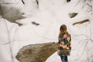 A woman walking in the snow in woodland.の写真素材 [FYI02252725]