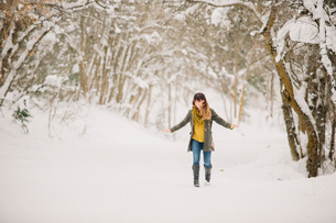 A woman walking in the snow in woodland.の写真素材 [FYI02252726]
