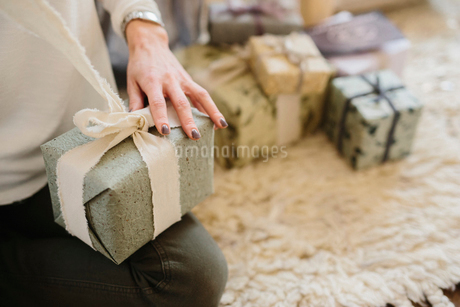 A woman sitting with a pile of wrapped presents.の写真素材 [FYI02252741]