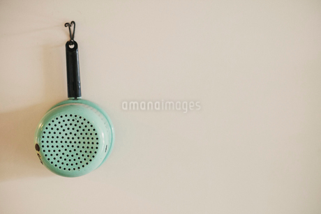 An enamel colander hanging on a wall, retro kitchen equipment.の写真素材 [FYI02252758]