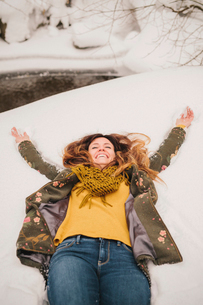 A woman lying on a snow bank with her arms stretched out.の写真素材 [FYI02252767]