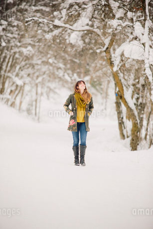 A woman walking in the snow in woodland.の写真素材 [FYI02252811]