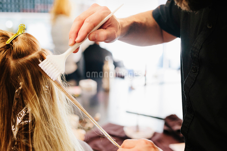 A hair colourist, a man using a paintbrush to cover sections of a woman's blonde hair.の写真素材 [FYI02252813]