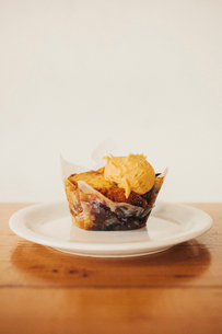 A fresh baked muffin with ice cream on a plate.の写真素材 [FYI02252815]