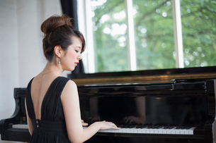 Young woman playing on a grand piano in a rehearsal studio.の写真素材 [FYI02252839]