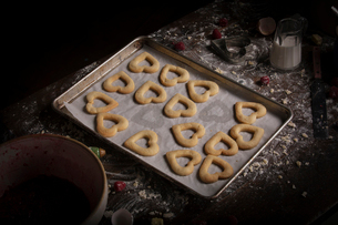 Valentine's Day baking, high angle view of a baking tray with heart shaped biscuits.の写真素材 [FYI02252845]