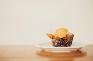 A fresh baked muffin with ice cream on a plate.の写真素材 [FYI02252846]