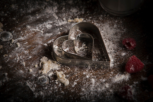 Valentine's Day baking, close up of a heart shaped biscuit cutter and fresh raspberries.の写真素材 [FYI02252853]