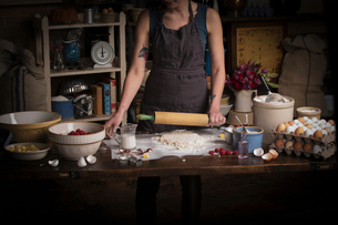 Valentine's Day baking, woman standing in a kitchen, rolling out dough with a rolling pin.の写真素材 [FYI02252855]