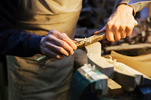 Man standing at a work bench in a carpentry workshop, working on a piece of wood secured in a benchの写真素材 [FYI02252858]