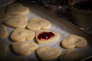 Valentine's Day baking, close up of a baking tray with heart shaped biscuits and raspberry jam.の写真素材 [FYI02252868]