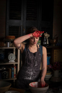 Valentine's Day baking, young woman standing in a kitchen, preparing raspberry jam, wiping her handの写真素材 [FYI02252869]