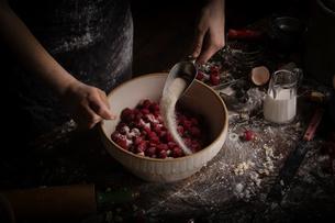 Valentine's Day baking, woman preparing fresh raspberries in a bowl, adding sugar.の写真素材 [FYI02252870]