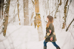 A woman walking in the snow in woodland.の写真素材 [FYI02252884]