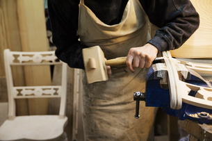 Man standing at a work bench in a carpentry workshop, working on a wooden chair with a wooden malletの写真素材 [FYI02252886]