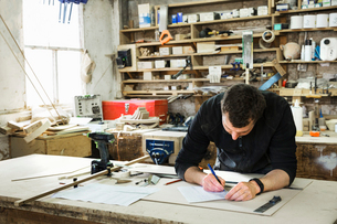 Man standing at a work bench in a carpentry workshop, writing a spreadsheet.の写真素材 [FYI02252897]