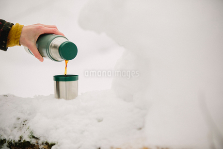 A person pouring a drink from a flask outdoors in the snow.の写真素材 [FYI02252917]