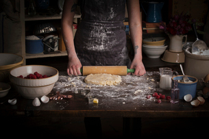 Valentine's Day baking, woman rolling out dough with a rolling pin.の写真素材 [FYI02252919]