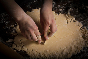 Valentine's Day baking, woman cutting out heart shaped biscuits from dough.の写真素材 [FYI02252930]
