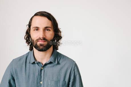 A young man with a beard in a blue shirt, looking at the camera.の写真素材 [FYI02252949]
