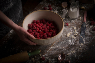 Valentine's Day baking. A bowl of fresh raspberries on a floury table.の写真素材 [FYI02252952]