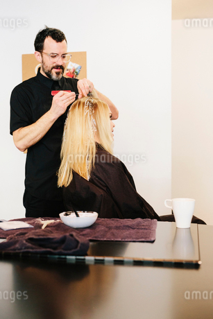 A hair colourist working with foils to give a client with long blonde hair highlights and lowlightsの写真素材 [FYI02252978]