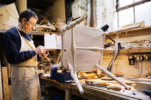 Man standing at a work bench in a carpentry workshop, working on a wooden chair.の写真素材 [FYI02253000]