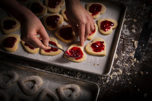 Valentine's Day baking, woman spreading raspberry jam on heart shaped biscuits.の写真素材 [FYI02253017]