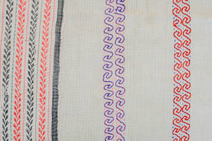 Full frame view of vintage fabric, embroidered with a scrolling pattern in red and purple, green andの写真素材 [FYI02253050]