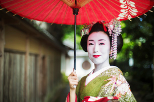 A woman dressed in the traditional geisha style, wearing a kimono and obi, with an elaborate hairstyの写真素材 [FYI02253054]