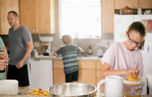 Family preparing breakfast in a kitchen.の写真素材 [FYI02253057]