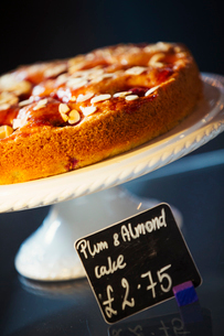 Specialist coffee shop. Plum and almond cake on a cake stand.の写真素材 [FYI02253069]
