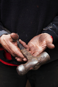 Close up of a blacksmith's hands, holding a metal hammer.の写真素材 [FYI02253095]