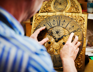 A clock maker displaying his work.の写真素材 [FYI02253119]