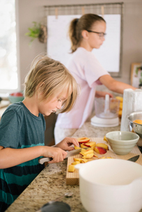 Family preparing breakfast in a kitchen, boy cutting fruit.の写真素材 [FYI02253122]